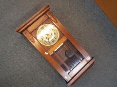 A wood cased, bevelled glazed wall clock, Arabic numerals to the dial, with key and pendulum,