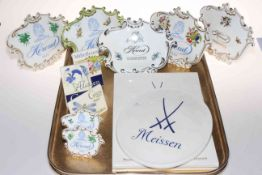 Collection of twelve china advertising display plaques, seven Herend, two Meissen and three Grien.