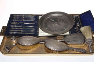 Three silver backed brushes, silver handled knives, button hooks, white metal dish, etc.