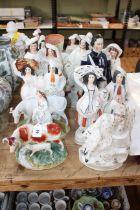 Twelve Victorian Staffordshire figurines including flatbacks, cattle, military, etc.