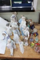 Twelve figurines including three Lladro and four Nao together with eleven glass paperweights and