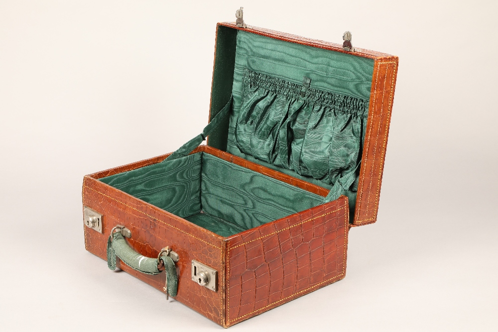 A fine crocodile leather suitcase, with an outer protective cover and green lining. 46cm long,