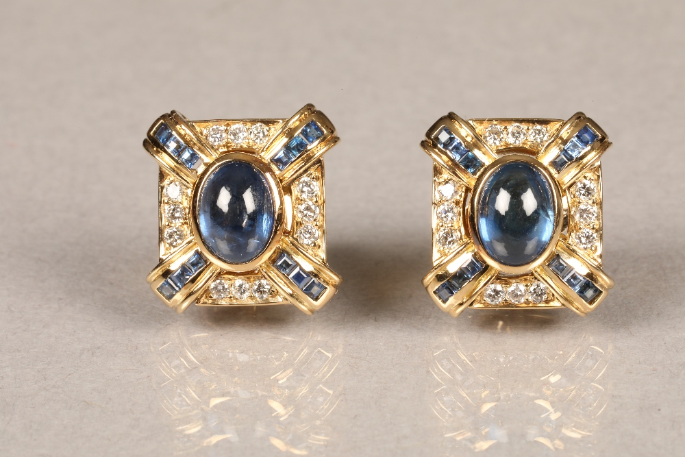Boxed pair of 18 carat gold earrings, each set with a central blue sapphire cabochon surrounded by