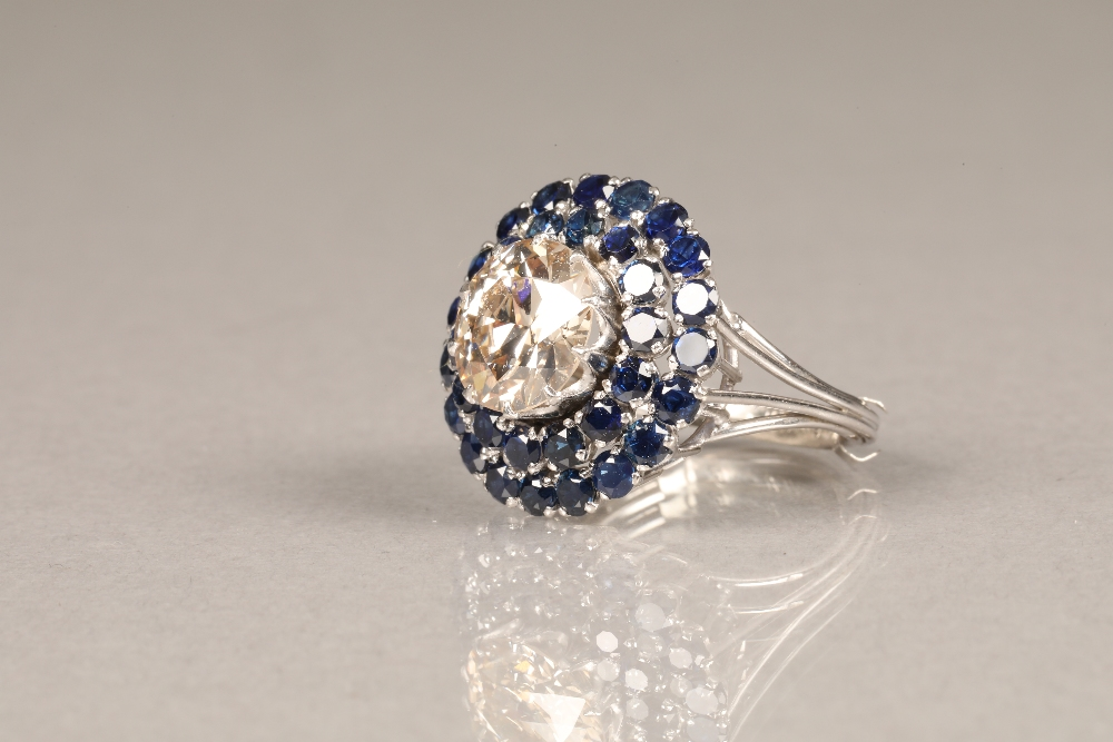 A diamond and sapphire three tiered circular cluster ring, centrally set with brilliant cut