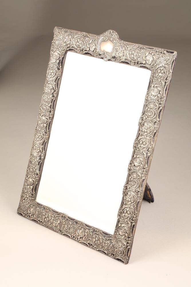 A silver mounted rectangular dressing mirror, the mount embossed with floral scrolls. The top with