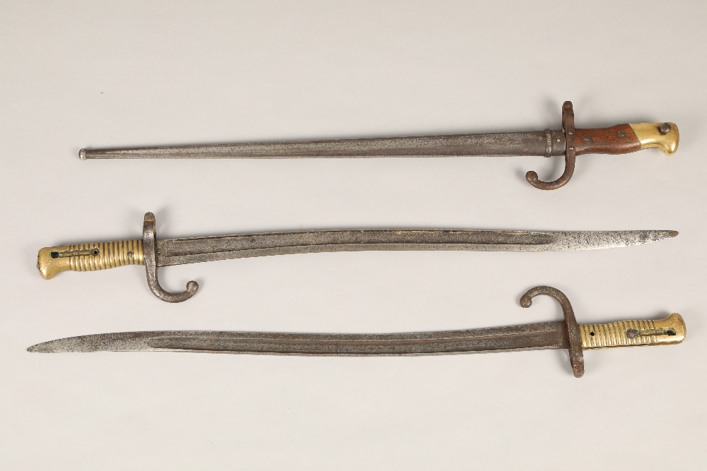 Three assorted French bayonets, two with brass grips without scabbards, and one with wood and