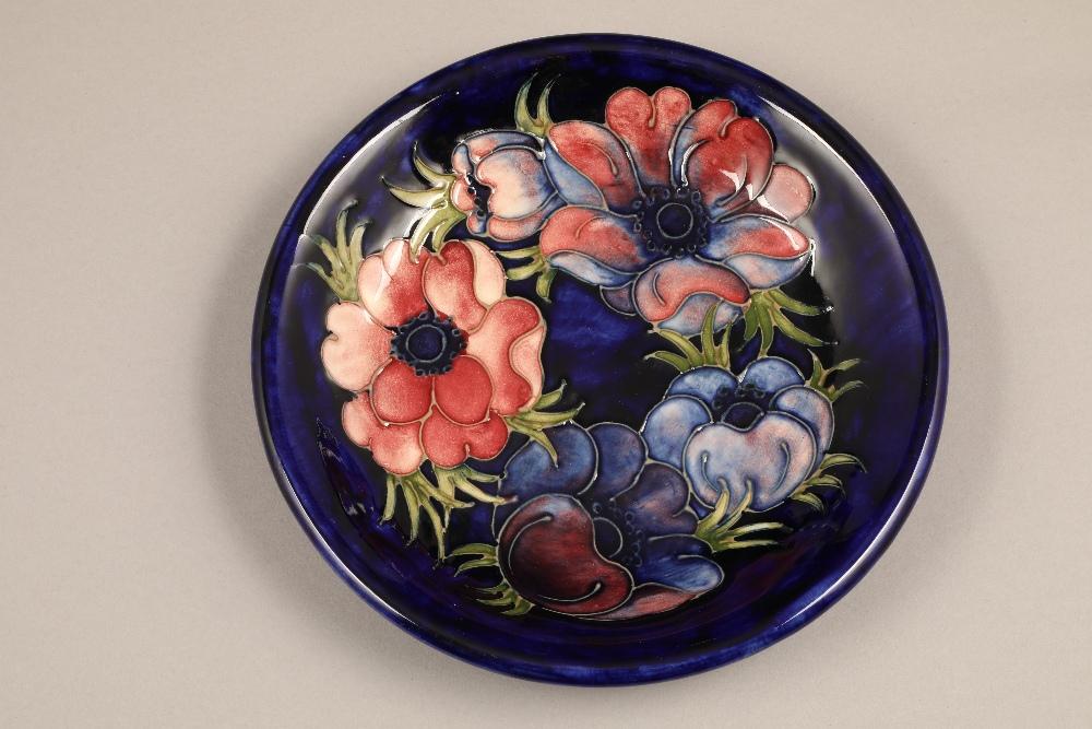 Moorcroft pottery dish, decorated in anemone design, on blue ground, signed William Moorcroft,