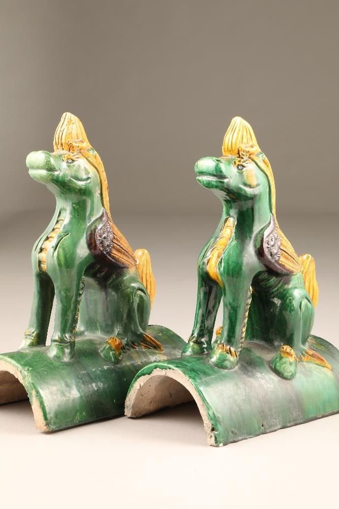 Pair of Chinese roof tiles in the form of heavenly horses in green, brown and yellow glaze, 24.5cm