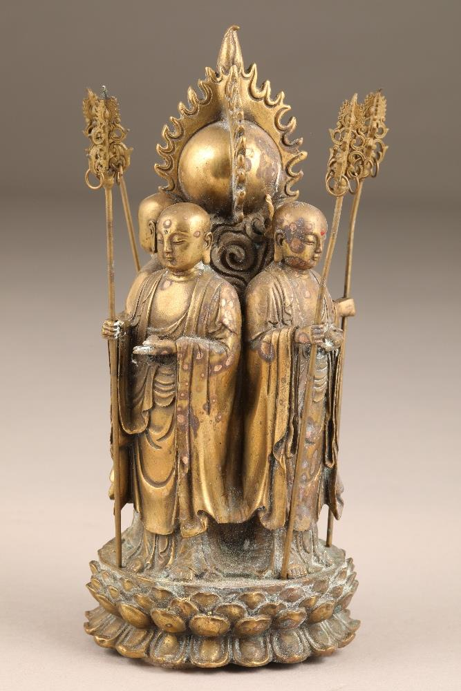 Chinese gilt bronze figure group of four Buddhist monks, standing with their backs to a flaming