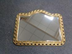 A shaped gilt framed bevelled mirror