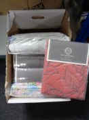 A box of new bedding including linen bed spread, quilt,