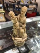 An antique carved ivory figure - Oriental gentleman with child
