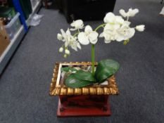 An oriental style planter containing artificial plants with pebbles.