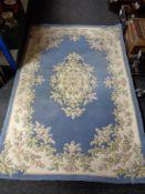 A floral woolen rug on blue ground,