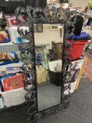A cotemporary bevel-edged hall mirror, in an elaborate black metal foliage design frame,