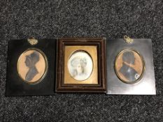 Two George III silhouette type miniatures together with a further portrait miniature behind glass.