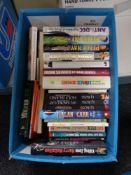 A box of books including Paul O'Grady,