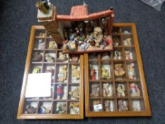 A collection of teddy bear figures in two display cases and a further display stand with miniature
