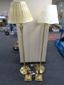 A pair of brass finished floor lamps together with a pair of brass table lamps