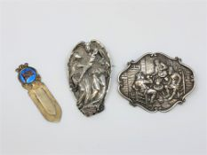 Two large ornate silver brooches and silver gilt clip.