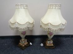 A pair of hand painted porcelain table lamps on brass bases with tasselled shades