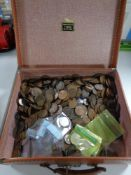 A vintage suitcase containing a large collection of coins,