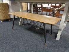 A mid 20th century low coffee table with metal under stretcher