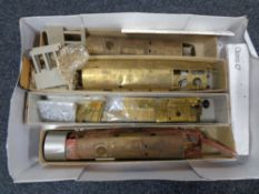 A box containing model railway, metal carriage and engine parts,