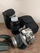 A Nikon F55 camera in case together with Nikon lens in fitted bag and other camera accessories