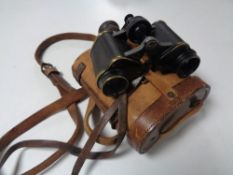 A pair of antique Helinox German binoculars in a fitted leather case.