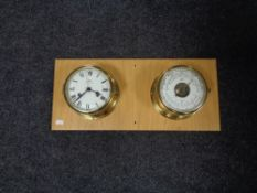 A brass cased ship's clock and barometer mounted on a board.