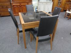 A contemporary Calligaris glass topped extending dining table together with a set of four black