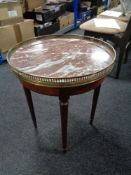 A circular mahogany marble topped occasional table with brass gallery.