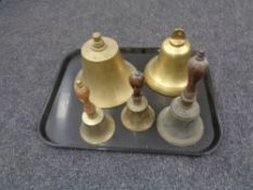 A tray containing two brass ship's style bells together with three further brass wooden handled