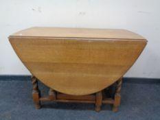 An Edwardian oak barley twist gate leg table.