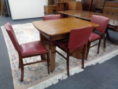 A mid 20th century walnut extending dining table together with a set of four chairs.