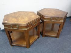 A pair of hexagonal two tier tables with brass handles and mounts.