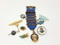 A group of silver and other badges