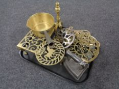 A tray of antique metal ware including brass trivets, fire dog, cast iron handled pan,