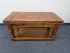 A contemporary hardwood two tier turnover top coffee table.