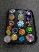 A tray of eighteen assorted glass paperweights
