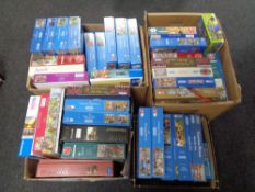 Three boxes containing a large quantity of assorted jigsaws.