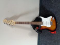 A Squier Strat by Fender electric guitar in carry bag.