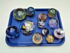 A tray of twelve assorted glass paperweights