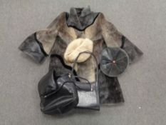A box containing a simulated fur coat with matching hat together with further hat and two leather