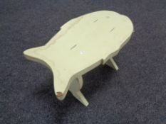 A painted cracket in the shape of a fish.