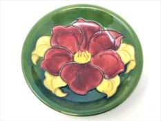 A Walter Moorcroft 'Clematis' pattern plate on green ground, Queen Mary Label, diameter 18.5cm.