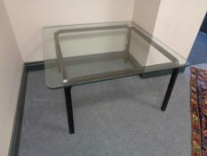 A square glass topped coffee table on painted wooden legs.