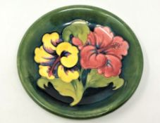 A Walter Moorcroft 'Hibiscus' pattern plate on green ground, Queen Mary Label, diameter 22cm.