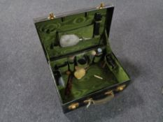 A green leather travel case containing three piece silver backed brush set and mirror,
